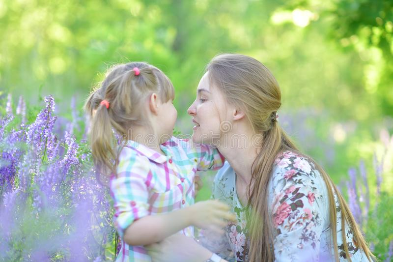Mother speaks to baby girl daughter, plays, grimacing, laughing royalty free stock photos