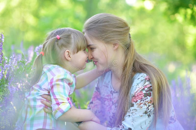 Mother speaks to baby girl daughter, plays, grimacing, laughing stock image