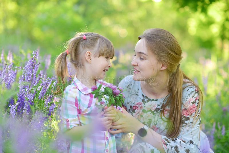 Mother speaks to baby girl daughter, plays, grimacing, laughing stock photo