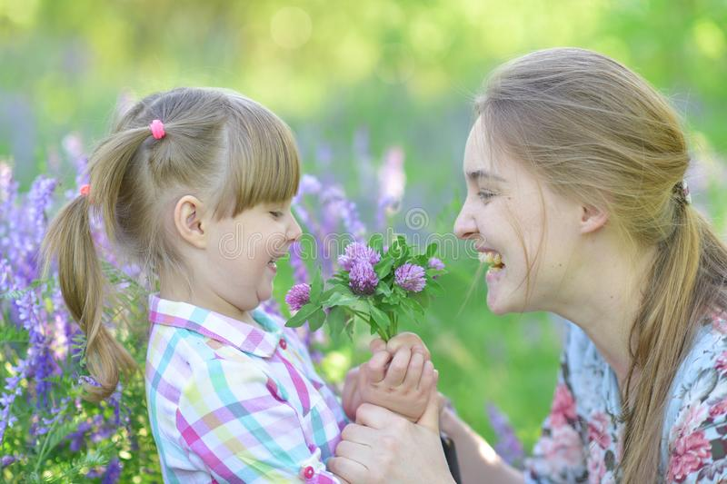 Mother speaks to baby girl daughter, plays, grimacing, laughing royalty free stock images
