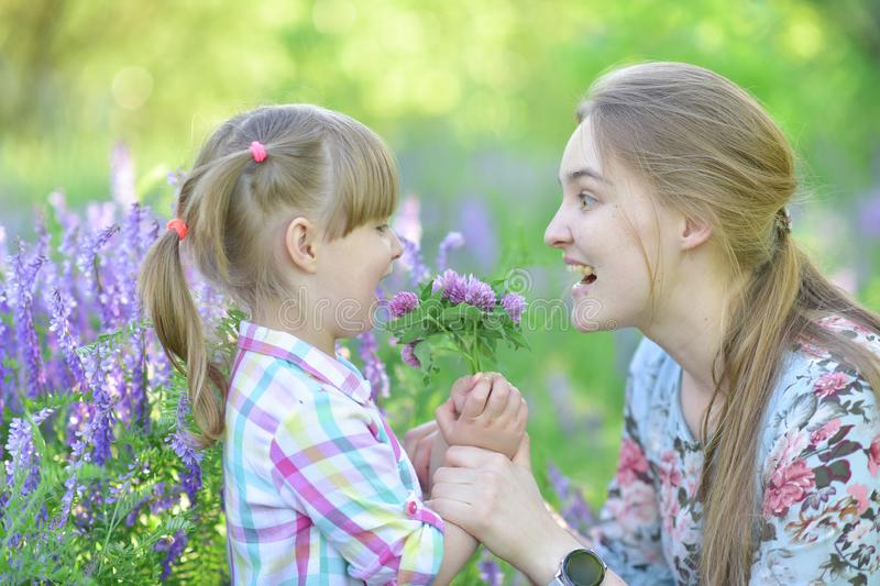 Mother speaks to baby girl daughter, plays, grimacing, laughing royalty free stock image
