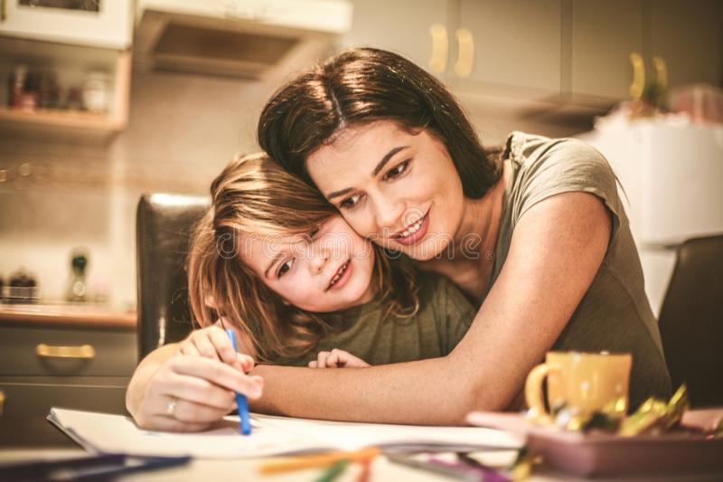 Mother spending time with daughter. Drawing a color book. Mother and daughter spending time together. Close up image stock images