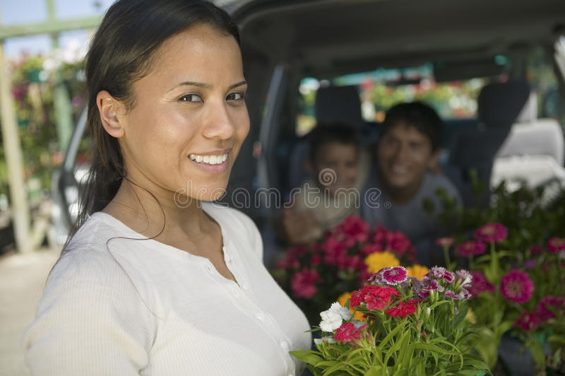 Mother standing by back of minivan holding flowers portrait stock photography