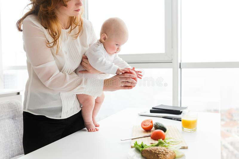 Mother standing and holding her cute little baby while showing him big red apple on kitchen royalty free stock images