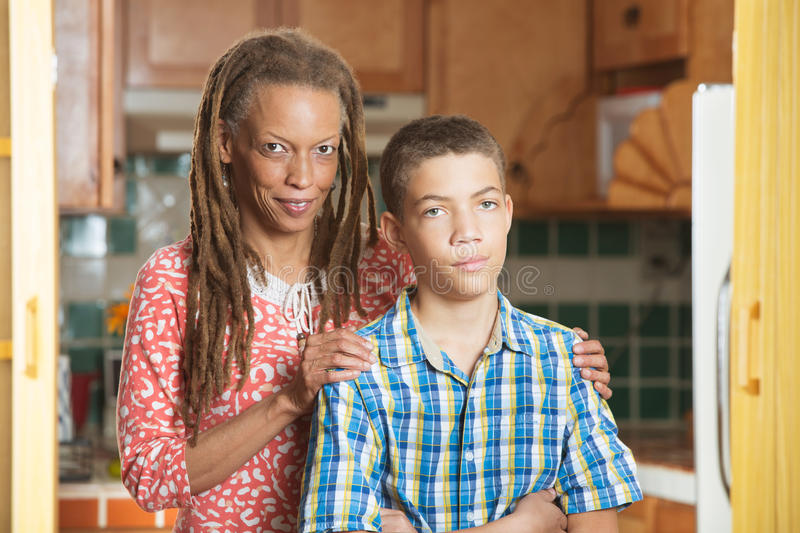Mother stands with her teen son with one hand on either shoulder royalty free stock photography