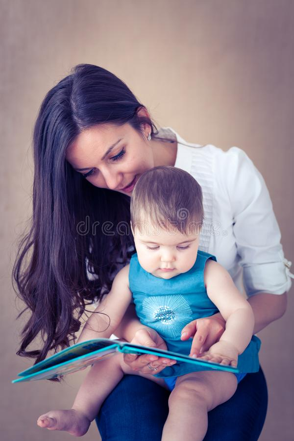 Mother story-telling to her baby girl stock photography
