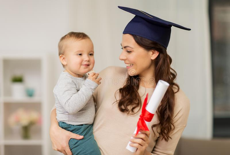 Mother student with baby boy and diploma at home stock photography