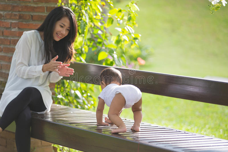Mother support her baby daughter to make her first step stock photo