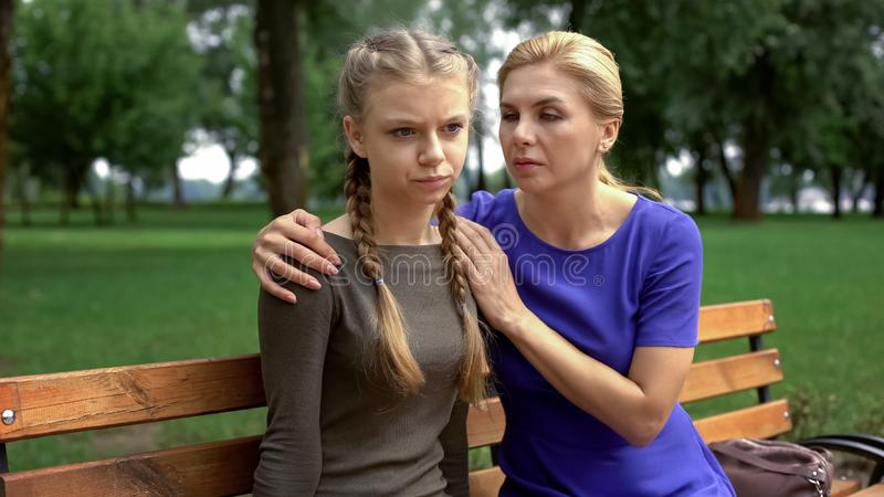 Mother supporting her upset daughter, problems with studying, adolescence. Stock photo royalty free stock photography