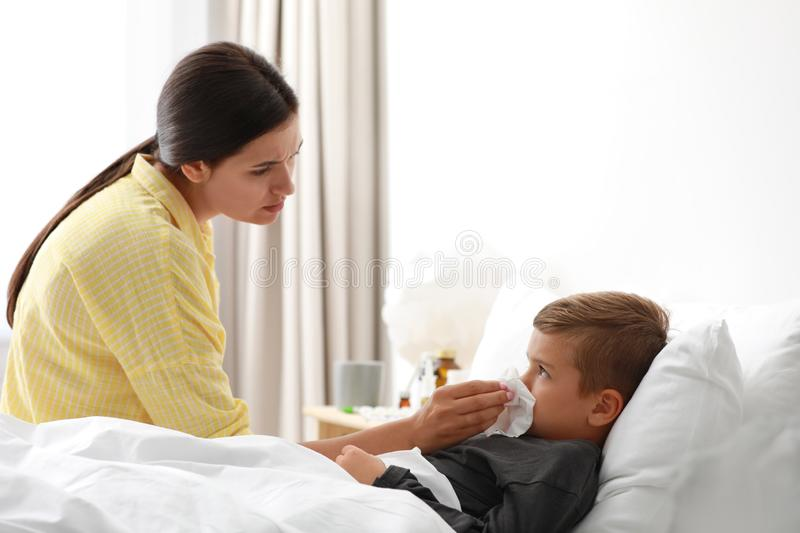 Mother taking care of her little son suffering from cold stock photos