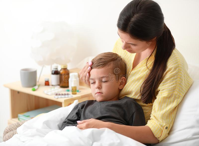 Mother taking care of her little son suffering from cold. In bed royalty free stock photo