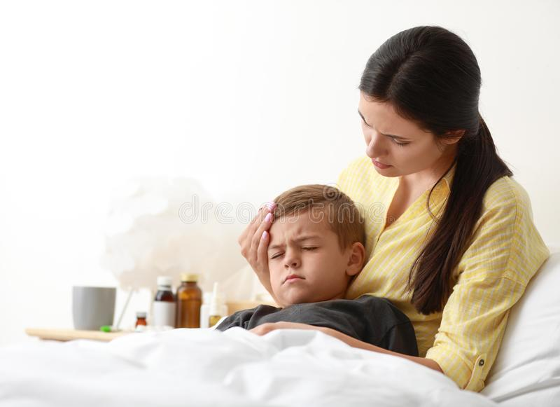 Mother taking care of her little son suffering from cold. In bed stock photos