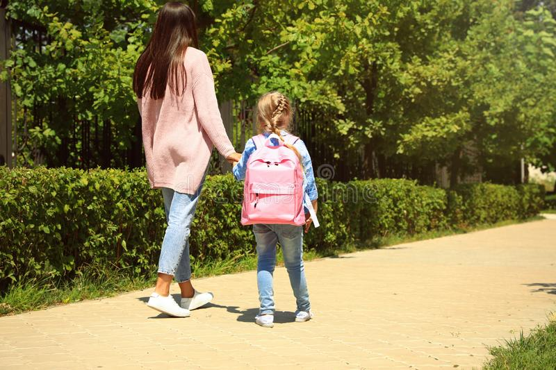 Mother taking her little child to school through park. Young mother taking her little child to school through park royalty free stock images