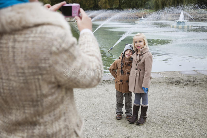 Mother Taking Photo Of Children In Front Of Fountain Stock Photography