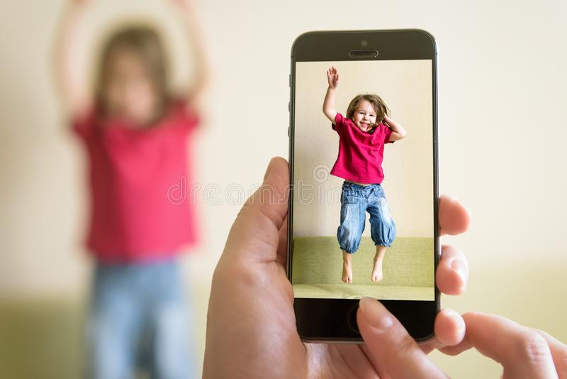 Mother taking photo of jumping baby girl with her mobile phone royalty free stock photography