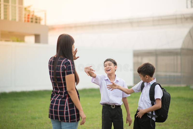 Mother taking sons to school together, hand wave say goodbye royalty free stock photography