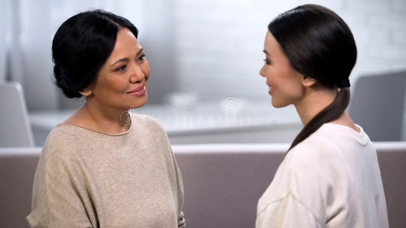 Mother talking to daughter, tenderly looking at her, giving advice, motherhood stock image