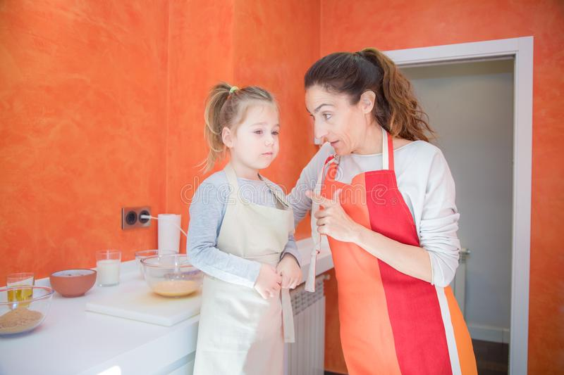 Mother talking to little girl cooking together in the kitchen stock photography