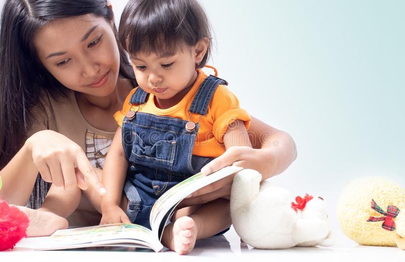 Mother teach child to read a book stock images