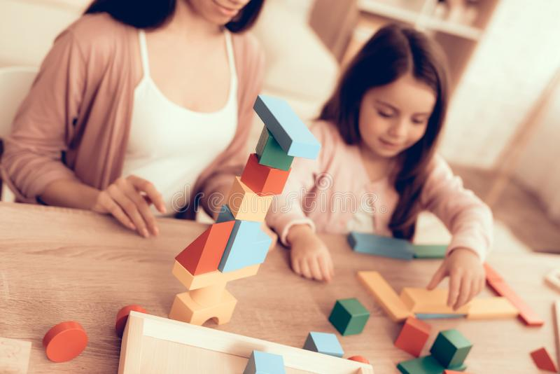 Mother Teaches Daughter Build House Cubes on Table stock photography