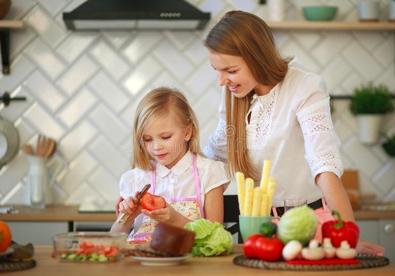 Mother teaches her child daughter how to cook in kitchen, parenthood and healthy lifestyle, nutrition stock photos