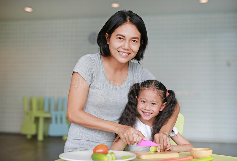 Mother teaches her children to cooking. Close up Asian mom and daughter slicing cucumber vegetable on chopping board at play room stock photography