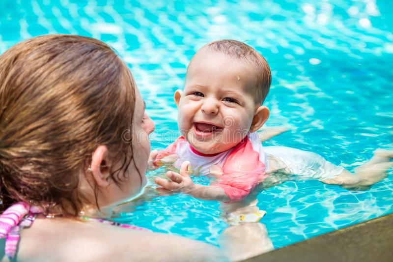 Mother teaches her little baby daughter to swim at the age of 8 months. Summer holiday with infant by the pool at the hotel. Happy stock photos