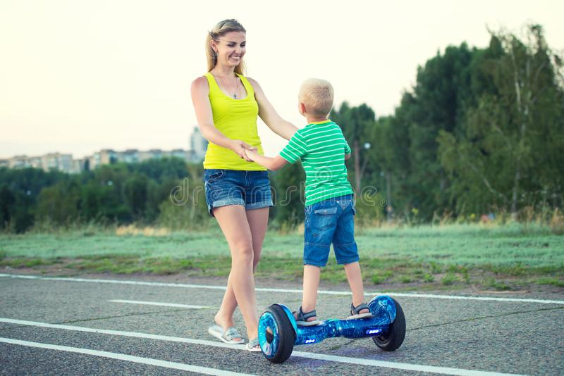 Mother teaches her little son to ride on balance board. stock photos