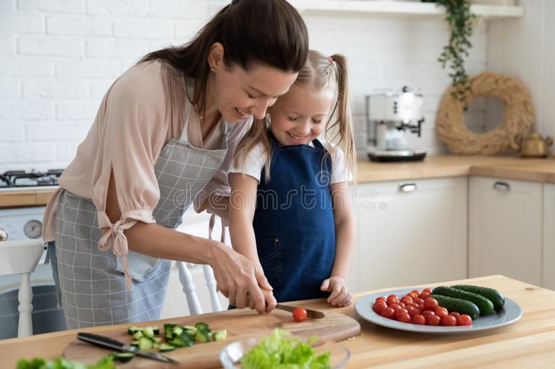 Mother teaches little daughter the basics of cooking stock photos