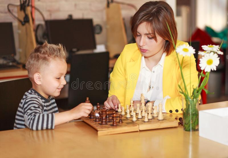 Mother teaches son play chess at home, parenting education stock photography