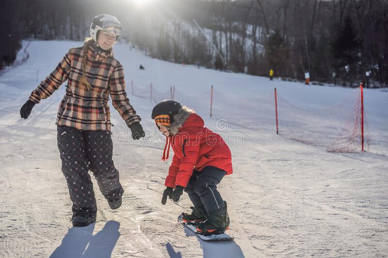 Mother teaches son snowboarding. Activities for children in winter. Children`s winter sport. Lifestyle.  stock image
