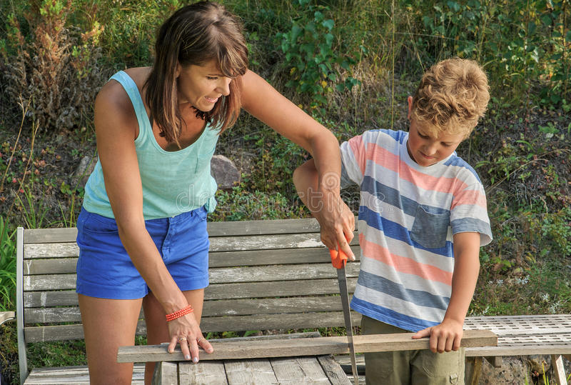 Mother teaches son to saw royalty free stock image