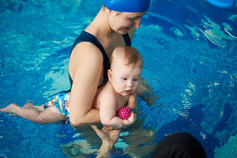Mother teaching baby boy swimming. Child first visiting swimming pool. Healthy family lifestyle concept. Top angle view royalty free stock images