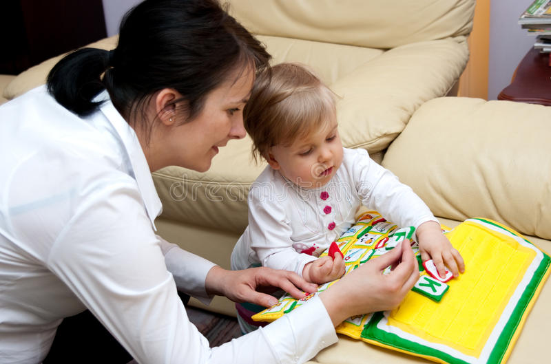 Mother teaching baby letters. Closeup of a mother teaching the letters of the alphabet to a baby girl royalty free stock photos