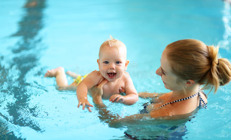 Mother teaching baby swimming pool stock photography