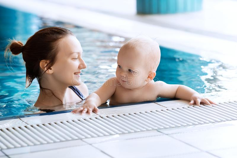 Smiling charming baby in swimming pool royalty free stock image