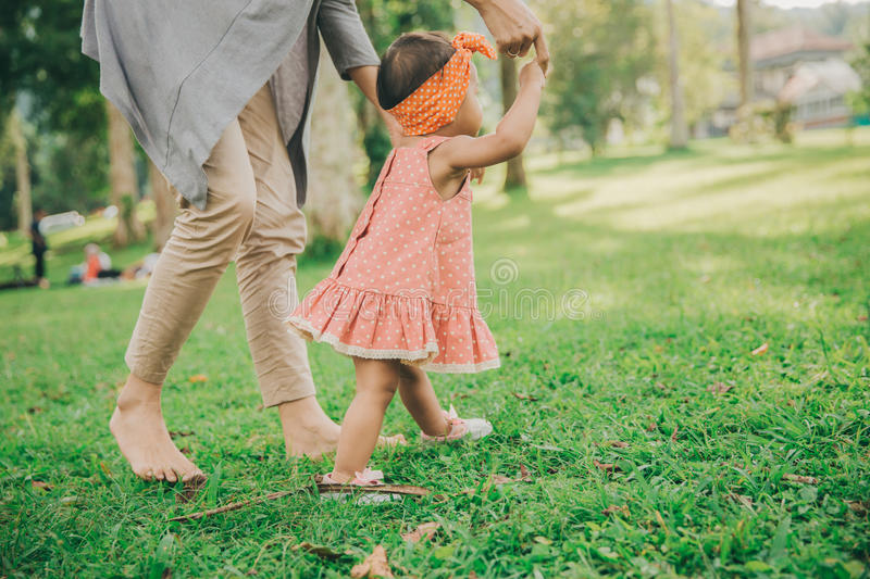 Mother teaching baby to walk in the park stock images