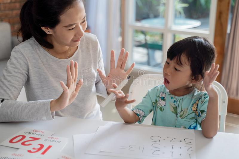 Mother teaching basic math to her little daughter royalty free stock image