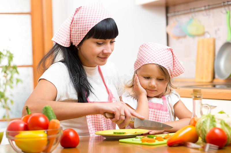 Mother teaching child making salad in kitchen. Mom and kid chopping vegetable on cutting board with knife. Cooking concept of royalty free stock image