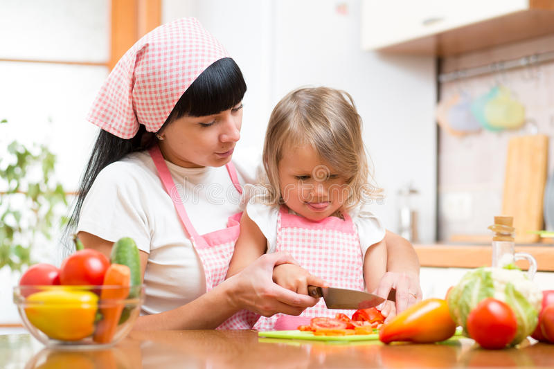 Mother teaching child making salad in kitchen. Mom and kid chopping vegetable on cutting board with knife. Cooking concept of. Mother teaching kid making salad stock photos