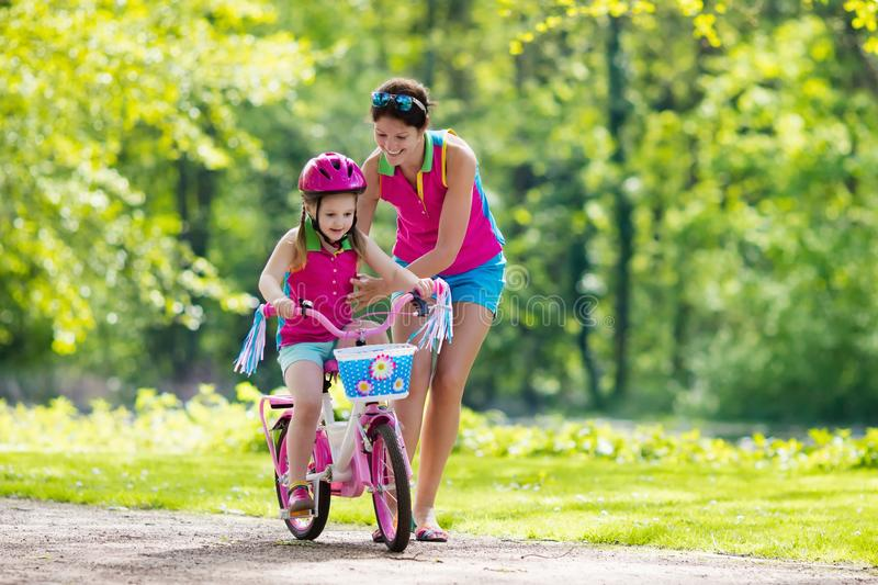 Mother teaching child to ride a bike royalty free stock images