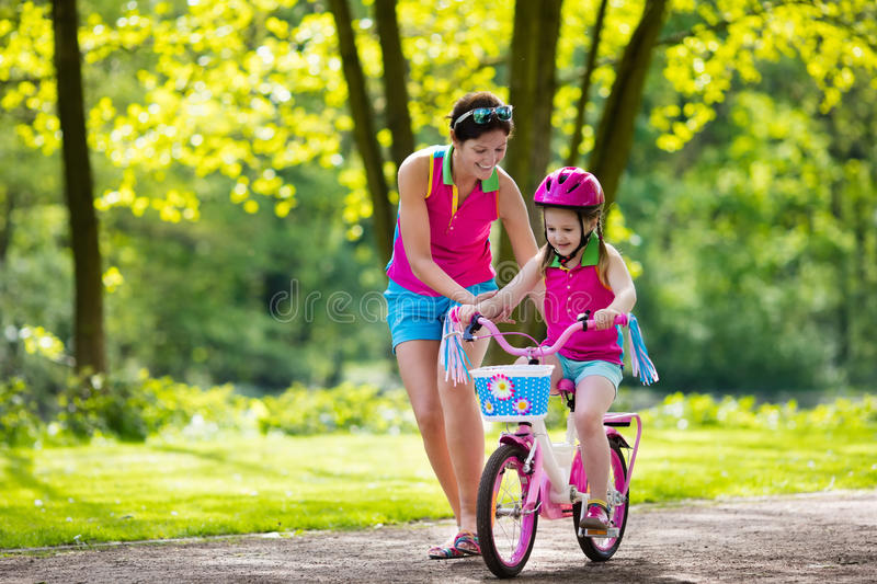 Mother teaching child to ride a bike royalty free stock photography