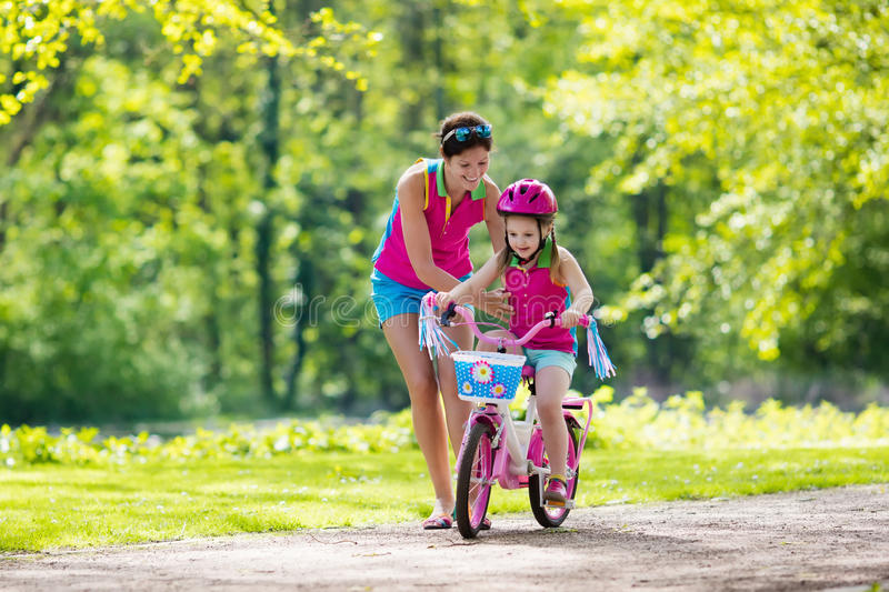 Mother teaching child to ride a bike stock photos