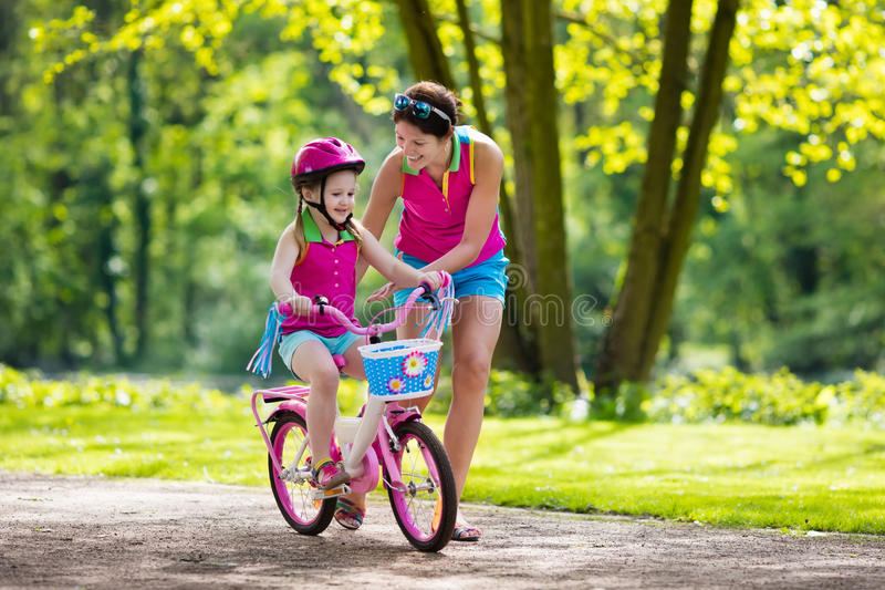 Mother teaching child to ride a bike stock images