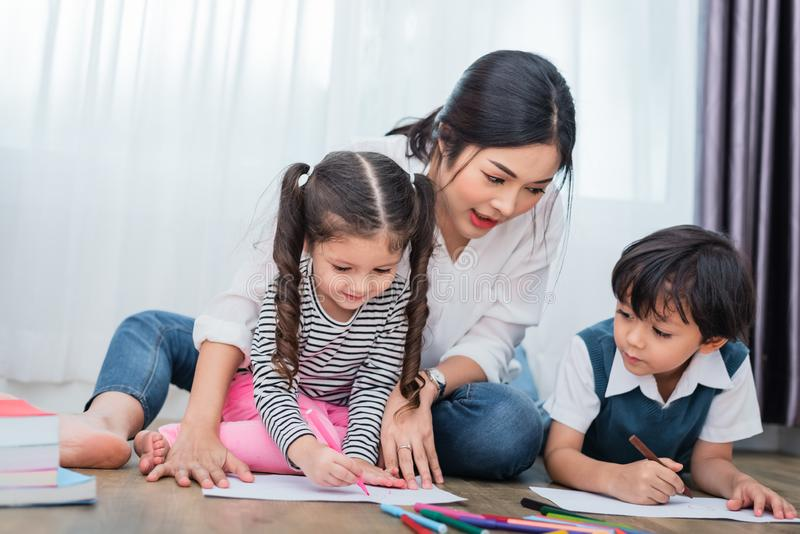 Mother teaching children in drawing class. Daughter and son pain. Ting with colorful crayon color in home. Teacher training students in art classroom. Education stock photo