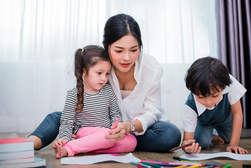 Mother teaching children in drawing class. Daughter and son painting with colorful crayon color in home. Teacher training students. In art classroom. Education royalty free stock photography