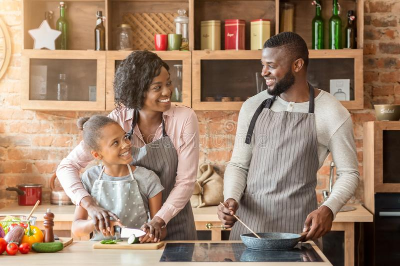 Mother teaching daughter cutting vegetables, father frying food stock photos
