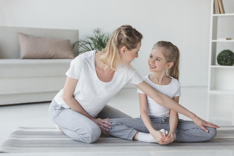 mother teaching daughter how to sit in yoga royalty free stock photos