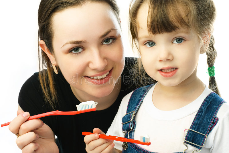 Mother teaching her daughter brushing teeth stock photo