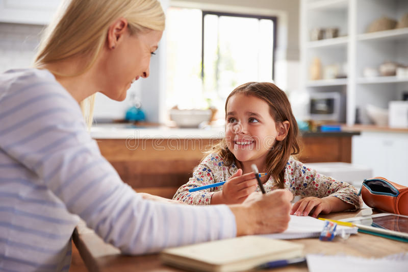 Mother teaching her daughter at home royalty free stock photos